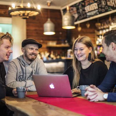 Fyra personer, tre män och en kvinna, sitter runt ett bord och ser mot en bärbar dator.