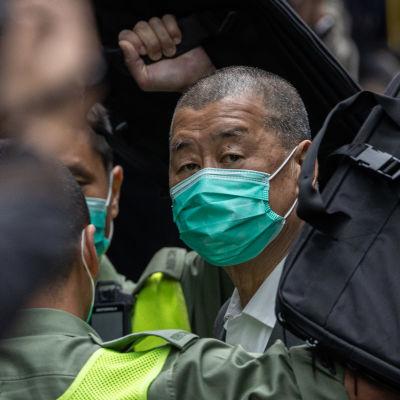 Miljonären Jimmy Lai eskorteras från häktet till domstol under hård polisbevakning.