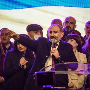 Nikol Pashinjan puhuu puhujalavalla, taustalla muita ihmisiä