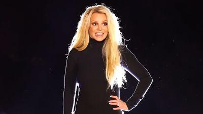 Britney Spears står på en scen. Hon poserar och ler medan hon tittar åt sidan.