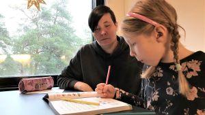 Äiti Renja Stenfors pitää kotikoulua tyttärelleen Tiia Holgerille JHL:n lakon vuoksi