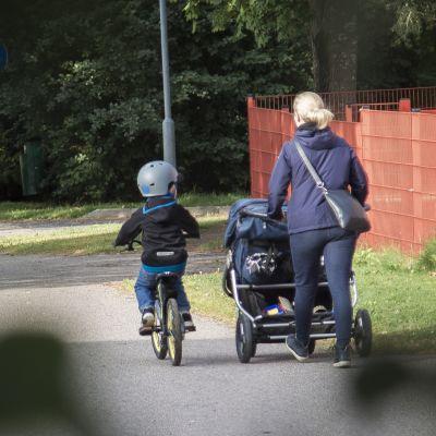 Äiti saattelee pyöräilevää lastaan kouluun Kangasalla.