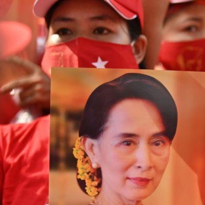 En kvinna klädd i rött håller i en bild på Myanmars  Aung San Suu Kyi