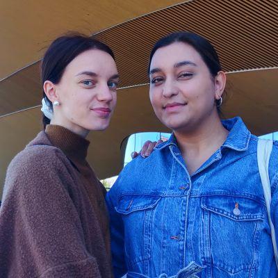 Emmi Hahto och Melissa Linsa står framför centrumbiblioteket Odes orangea fasad i Helsingfors,