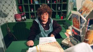 Vaapukkalan Olga, Vaapukkalan Puotipostin tomera postimestari Olga P. Postinen (Ritva Valkama) varustautuu joulukiireisiin. Kuvaus pvm : 19960916
