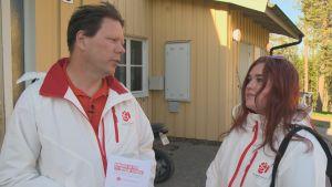 Två personer i vita rockar med Socialdemokraternas logo i ett bostadsområde.