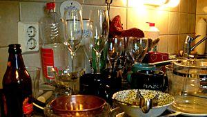 Flaskor och glas och kärl på ett diskbord.