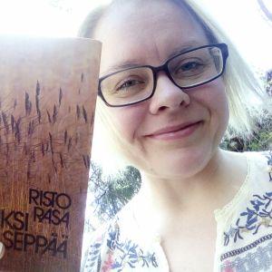 Kirjamielellä-bloggaaja pitää kädessään Risto Rasan kokoelmaa Kaksi seppää