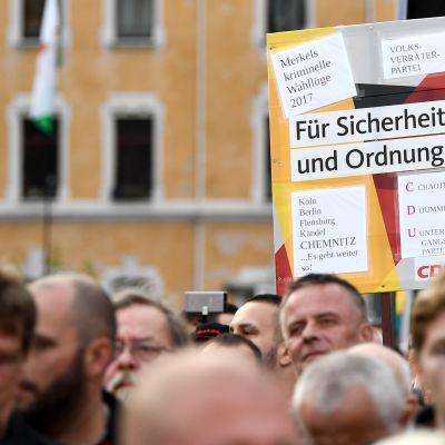 """Tyska invandringskritiska demonstranter i Chemnitz håller upp plakat med texten """"För säkerhet och ordning""""."""