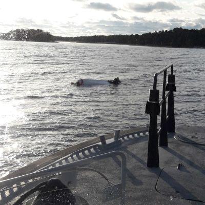 Några personer klamrar sig fast vid en båt som kantrat. I förgrunden syns fören av Sjöbevakningens båt, från vilken bilden togs.