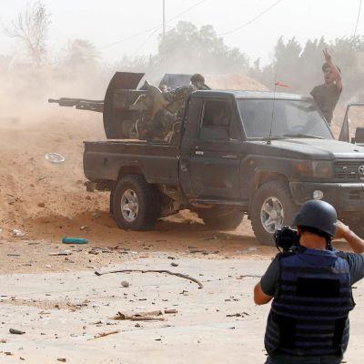 En journalist fotograferar striderna i utkanten av Libyens huvudstad Tripoli