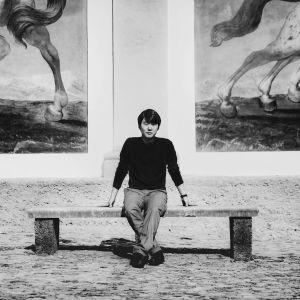 pianisti Seong-Jin Cho istuu suurten taideteosten edessä