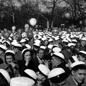 Paljon ylioppilaslakkisia ihmisiä juhlimassa vappua ulkona.