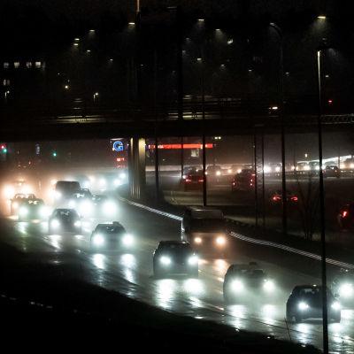 Bilar på en mörk väg.