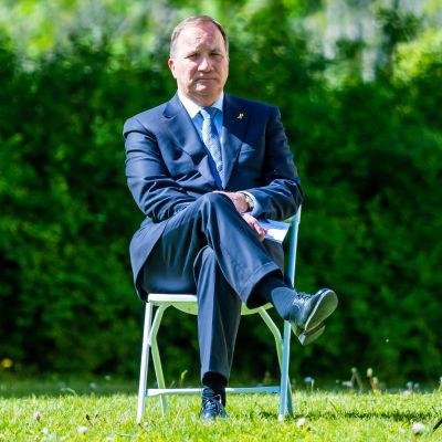 Stefan Löfven sitter på en stol på en gräsmatta. Han sitter med benen i kors och är klädd i kostym.
