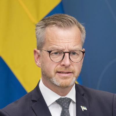 Inrikesminister Mikael Damberg vid regeringskansliets presspodium med svenska flaggor i bakgrunden.