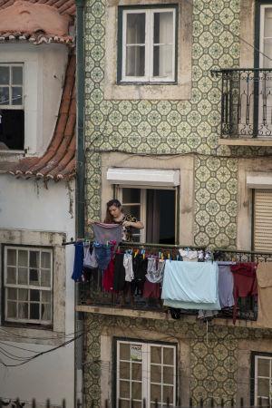 En kvinna hänger upp tvätt på en balkong till ett gammalt hus i Lissabon.