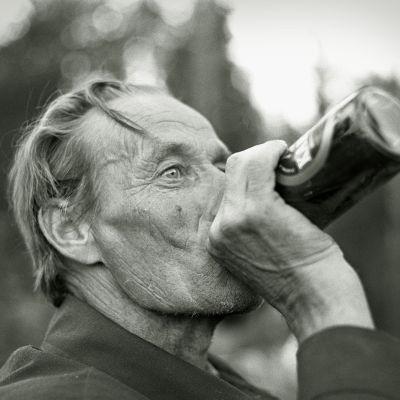 Mies juo olutta metsässä