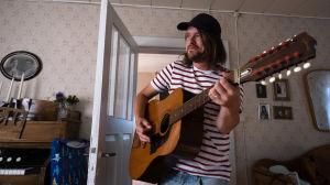 Vit man med randig t-shirt och keps spelar gitarr.