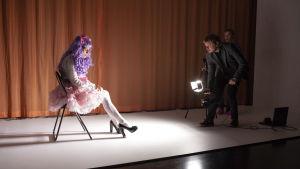 Lotta Kaihua, Paavo Kinnunen ja Pirjo Lonka näyttelevät outoja naapureita. Lolita-asuinen nainen istuu tuolilla, mies valaisee häntä spottivalolla.