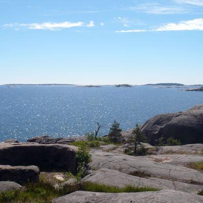En bergsklippa med utsikt över hav.