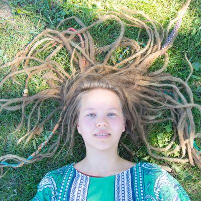 Katriina Loisa makaa nurmikolla rastat levällään.