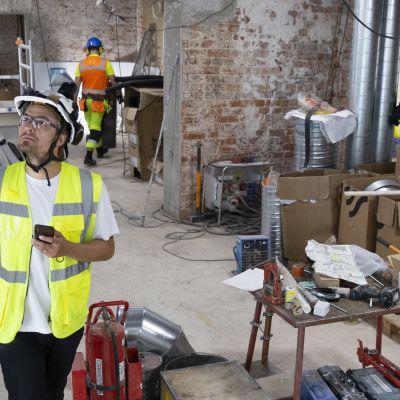 Lari Sorsa kävelee rakennustyömaalla kypärä ja joka suuntaan kuvaava pieni kamera päässään.