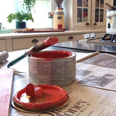 En pensel som doppats i i rosa färg är ställd mot en öppnad burk med målarfärg. Målarfärgsburken står på en köksbänk som är täckt med tidningspapper. I bakgrunden står en kastrul på spisen.