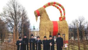 Sju herrar i cylinderhatt och svarta kappor står framför Gävles jättelika halmbock.