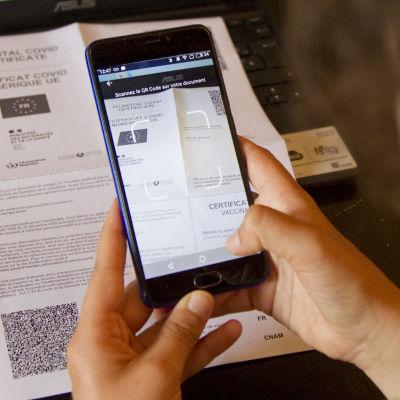 En kvinna tar en bild på ett papper med en QR-kod för att ladda upp sitt coronaintyg till coronapassappen.