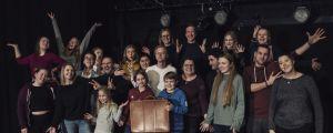 Ett gäng skådespelare står samlade på en scen och ser glada ut.