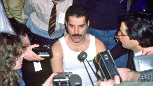 Freddie Mercury toimittajien ympäröimänä 1984