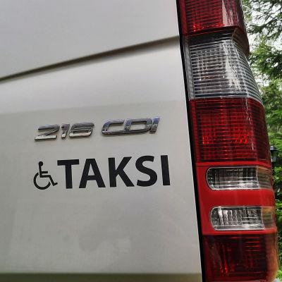 Rullstolssymbol och ordet Taksi i bakändan på en stor taxibil.