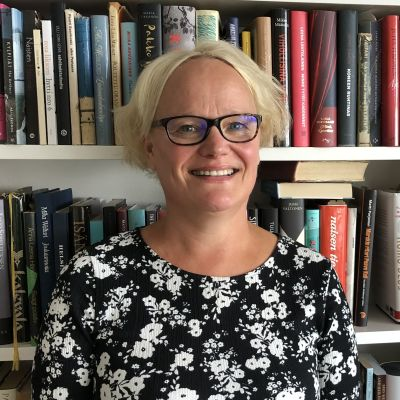 En blond kvinna står framför en bokhylla.