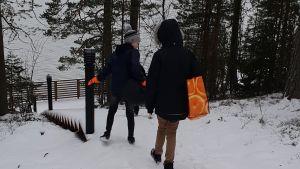 barn går i snö genom skog mot strand