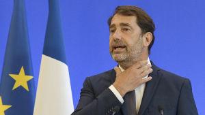 Frankrikes inrikesminister Castaner håller sig om halsen.