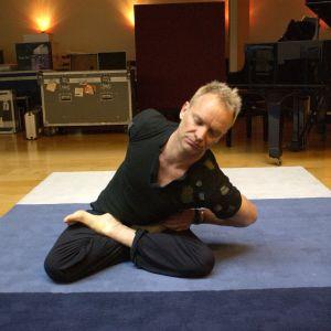 Sting yogar i konstig ställning på yogamaddrass.