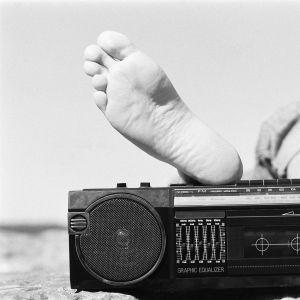 Jalat rannalla matkaradion päällä.
