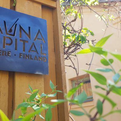 Keltaisen puutalon seinässä sininen kyltti, jossa lukee: Sauna Capital, Tampere Finland