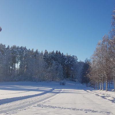 Kuumailmapallo taivaalla lumisen maiseman yllä