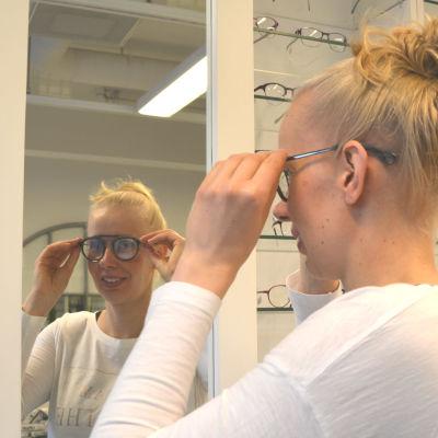 Kvinna provar glasögon framför spegel.
