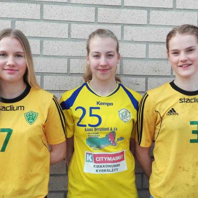 Tre tjejer står uppradade med sina speltröjor på.