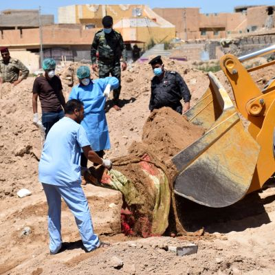 Viranomaiset tutkivat Ramadista Irakista löytynyttä joukkohautaa. Kaivinkone nostaa maasta hiekkaa, jonka joukosta paljastuu verisen näköinen kangas. Maskeilla suojatuneet viranomaiset seuraavat tilannetta.