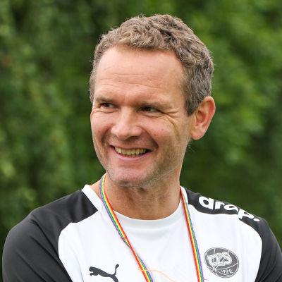 Jonatan Johansson, fotbollstränare för TPS herrlag, står och ler med