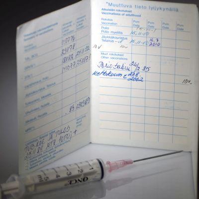 Stelkrampsvaccinsspruta fotad med ett vaccinkort i bakgrunden.