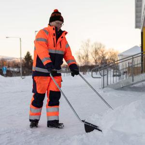 Tapio Guttorm työntää lunta kolalla.