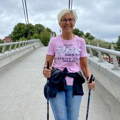 En medelålders kvinna i jeans och ljusröd t-skjorta stavgår över gångbron i Borgå. Hon tittar in i kameran och ler.