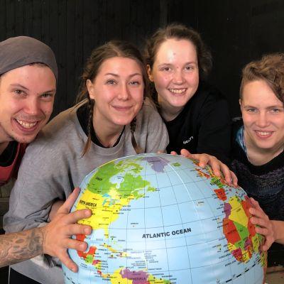 Neljä nuorta näyttelijää pitelee kiinni karttamaapallosta ja hymyilee.