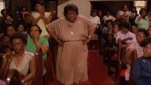 Vanhahko musta nainen tanssii kirkon käytävällä. Kuva dokumentista.