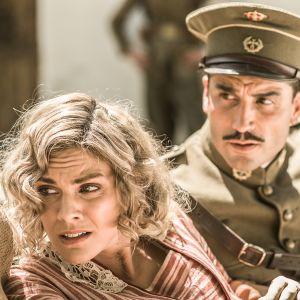 Nainen ja mies istuvat ilmeisesti vaunuissa, miehellä sotilaspuku, nainen katsoo vasemmalle tuskastuneen näköisenä.